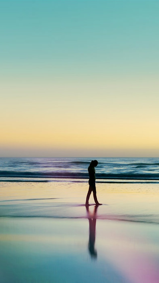 A Woman Silhouetted At The Beach
